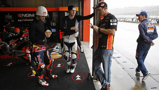 Americký motocyklista Colin Edwards (druhý zprava) a Australané Jack Miller (třetí zprava) a Arthur Sissis v garážích na okruhu Motegi v japonském Tokiu.