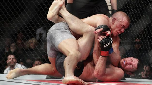 Georges St-Pierre (nahoře) a Michael Bisping. Pár sekund a GSP mohl slavit.