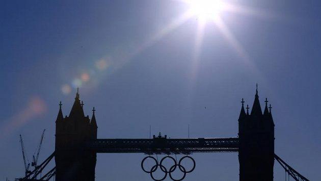 Rozžhavený sluneční kotouč nad mostem Tower Bridge. Jednu z londýnských dominant během her zdobí olympijské kruhy.
