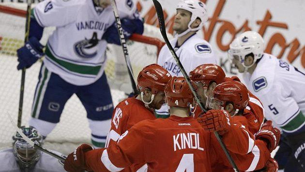 Obránce Detroitu Jakub Kindl (číslo 4) oslavuje se spoluhráči gól Pavla Dacjuka v síti Vancouveru.