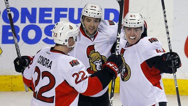 Hokejisté Ottawy (zleva Erik Condra, Cory Conacher a střelec vítězného gólu Jean-Gabriel Pageau) se radují v utkání proti Bostonu.