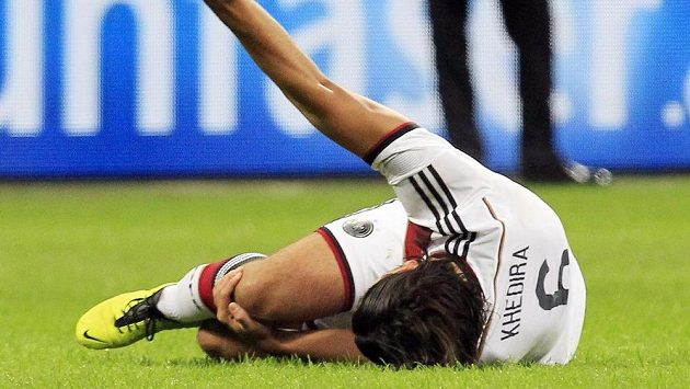Německý fotbalista Sami Khedira se po svém zranění v přátelském utkání s Itálií svíjí na trávníku.