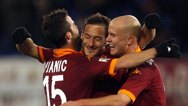Útočník AS Řím Francesco Totti (uprostřed) se raduje se spoluhráči Miralemem Pjaničem (vlevo) a Michaelem Bradleym z gólu.
