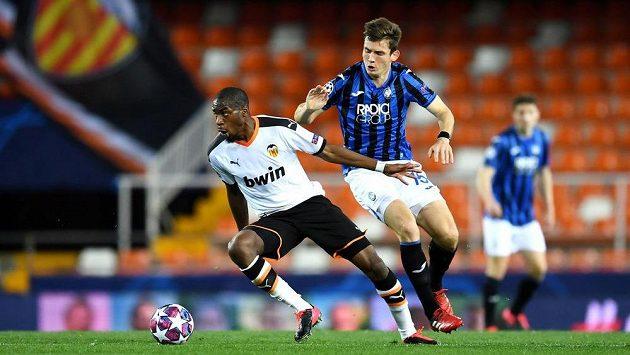 Geoffrey Kondogbia (vlevo) z Valencie v souboji o míč s Martenem de Roonem z Atalanty Bergamo. Ve Španělsku už se hrálo bez diváků.