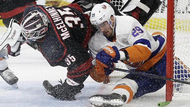 Brock Nelson z New Yorku Islanders v tvrdém souboji s brankářem Caroliny Curtisem McElhinneym.
