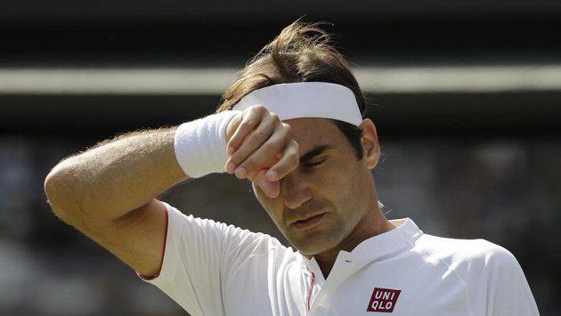 Roger Federer si otírá čelo při zápase s Kevinem Andersonem.