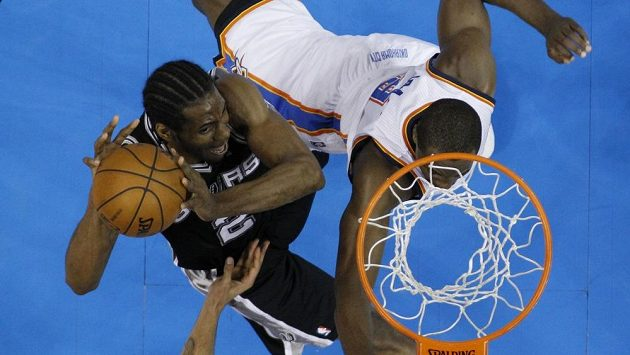 Kawhi Leonard ze San Antonia Spurs střílí koš před bránícím Sergem Ibakou z Oklahoma City Thunders.