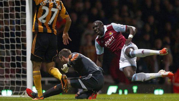 Brankář Hullu Allan McGregor (vlevo dole) fauluje Mohameda Diameho z West Hamu United ve středečním utkání anglické Premier League.