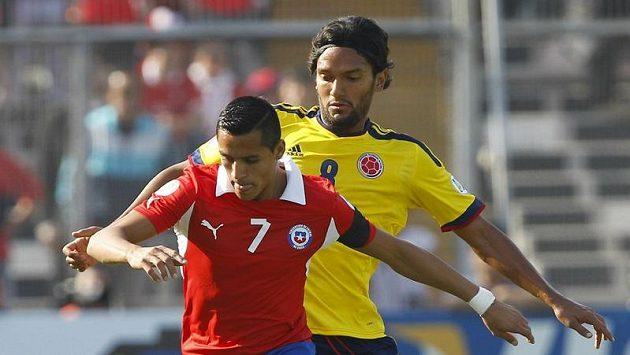 Chilský útočník Alexis Sánchez (v červeném) v kvalifikačním utkání o postup na MS 2014 proti Kolumbii.