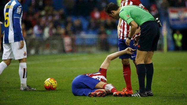 Záložník Atlétika Tiago Mendes leží na zemi během zápasu s Espaňolem. Madridskému celku bude chybět čtyři měsíce.