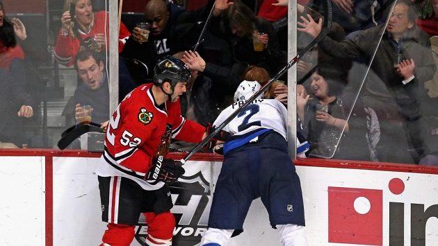 Útočník Chicaga Brandon Bollig (52) atakoval Adama Pardyho z Winnipegu tak tvrdě, že ho prohodil plexisklem mezi překvapené fanoušky Blackhawks.