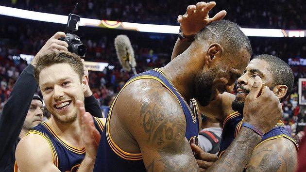 Opory Clevelandu Cavaliers' LeBron James (23) Kyrie Irving (vpravo) a Matthew Dellavedova (8) se radují z postupu do finále Východní konference NBA.
