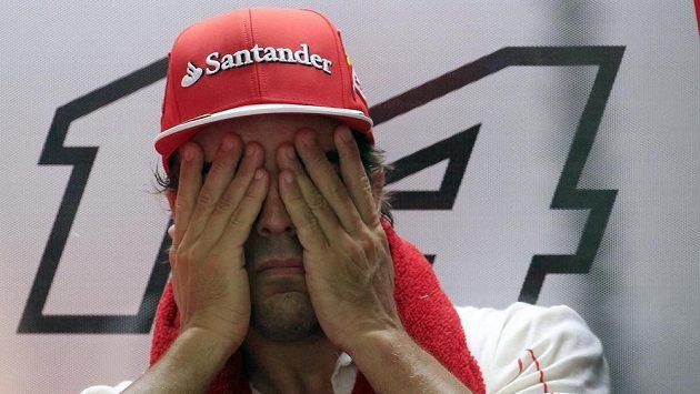 Pilot Ferrari Fernando Alonso stírá pot z obličeje při měřeném tréninku v Sepangu.