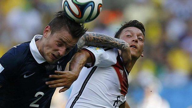 Francouzský obránce Mathieu Debuchy (vlevo) v souboji se svým budoucím spoluhráčem z Arsenalu Mesutem Özilem během čtvrtfinálového duelu na MS v Brazílii.