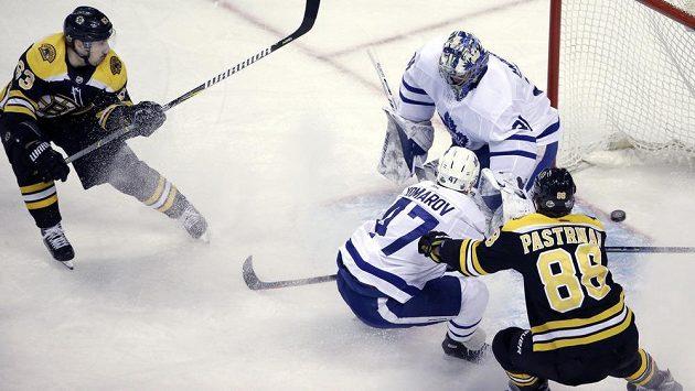 Bostonský Brad Marchand (63) překonává gólmana Toronta Maple Leafs Frederika Andersena (31). Obránce Leo Komarov (47) se snaží zastavit Davida Pastrňáka.
