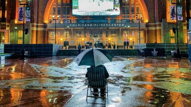 Fanoušek Dallasu Stars sledoval čtvrtý zápas čtvrtfinálové série na velkoplošné obrazovce před halou navzdory silnému dešti.
