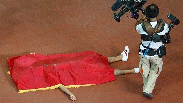 Pod svou národní vlajkou vychutnává Hicham El Guerrouj vítězství na MS v běhu na 1500 metrů roku 2003.