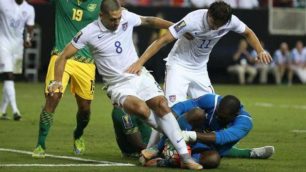 Jamajský brankář Ryan Thompson zachraňuje před Američany Clintem Dempseym (8) a Alejandrem Bedoyou (11) v semifinále Zlatého poháru.