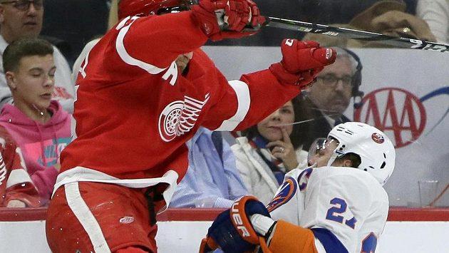 Zadák Detroitu Niklas Kronwall sráží na led útočníka New Yorku Islanders Anderse Leeho.