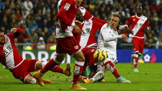 Záložník Realu Madrid Luka Modrič (vpravo) bojuje proti přesile fotbalistů Rayo Vallecano.