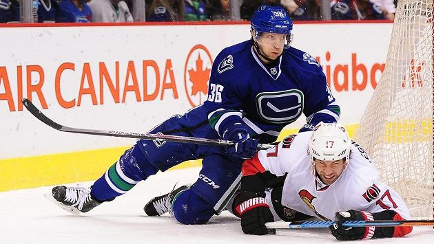 Dánský útočník Jannik Hansen (nahoře) z Vancouveru atakuje Davida Legwanda z Ottawy.