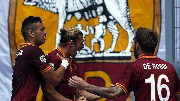 Federico Balzaretti (uprostřed) se raduje se svými spoluhráči z AS Řím Danielem De Rossim (vpravo) a Leandrem Castanem z gólu do sítě Lazia.