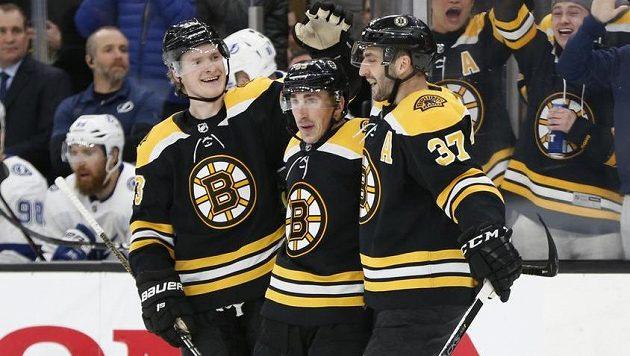 Hokejisté Bostonu Bruins slaví. Brad Marchand (63), Danton Heinen (43) a centr Patrice Bergeron (37) si užívají poté, co gólman Tampy Bay Lightning Louis Domingue inkasoval gól.