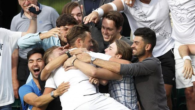 Brit Marcus Willis v obejtí svých nejbližších po senzační výhře ve Wimbledonu.