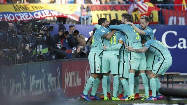 Fotbalisté Barcelony oslavují trefu Lionela Messiho na hřišti Atlétika Madrid.