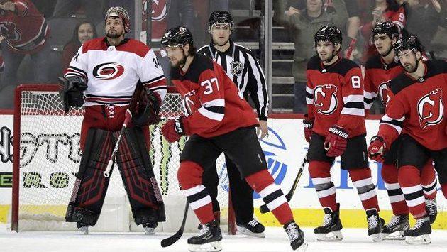Brankář Caroliny Hurricanes Petr Mrázek, sleduje radost hokejistů New Jersey Devils poté, co jej překonal český útočník Pavel Zacha (37)