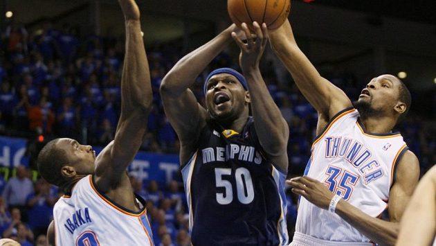 Basketbalisté Oklahomy Serge Ibaka (vlevo) a Kevin Durant (vpravo) brání při střelbě Zacha Randolpha z Memhisu.