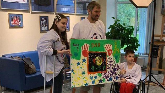 Hvězdný hokejový útočník Alexandr Ovečkin s obrazem, který za pomoci dětí namaloval.