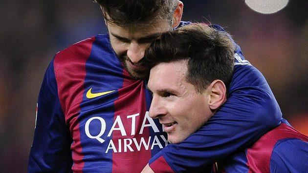 Obránce Barcelony Gerard Pique a útočník Lionel Messi se na ilustračním snímku radují z výhry 2:1 v ostře sledovaném derby nad Realem Madrid.