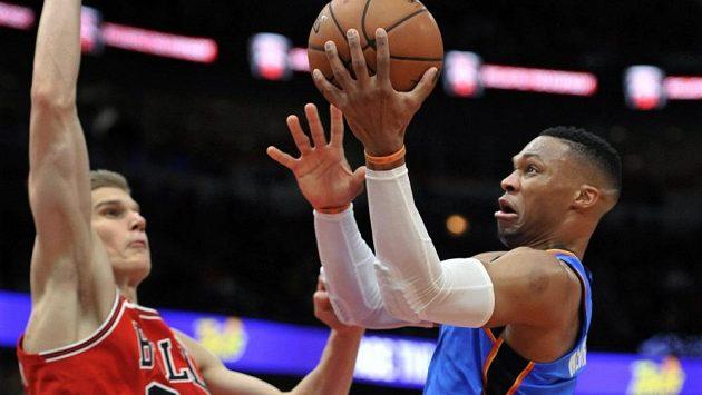 Basketbalista Oklahomy Russell Westbrook zakončuje přes Lauriho Markkanema z Chicaga.