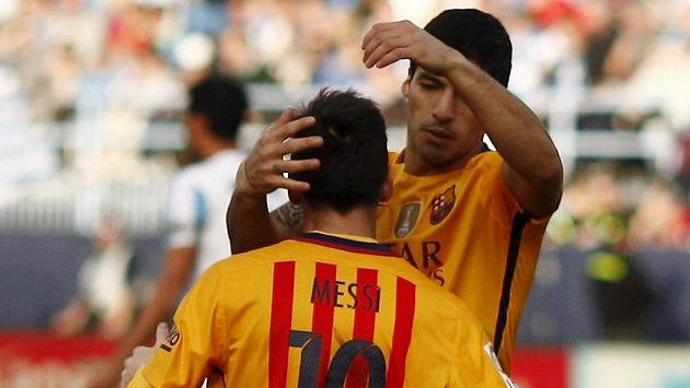 Lionel Messi (zády) a Luis Suárez slaví vítězný gól Barcelony v Malaze.
