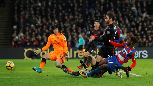 Wilfried Zaha (vpravo) z Crystalu Palace střílí na branku Arsenalu, vlevo brankář Petr Čech.