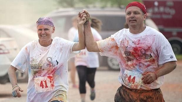 Kim Brighamová drží za ruku svého manžela Roba při nedělním závodě, který byl uspořádán na její podporu v boji s rakovinou.