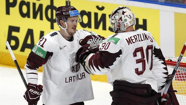 Lotyšský útočník Rudolfs Balcers a gólman Elvis Merzlikins se radují po zápase s Nory.