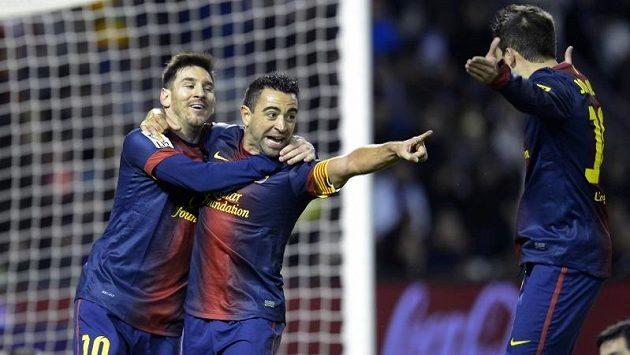 Fotbalisté Barcelony (zleva) Lionel Messi, Xavi Hernandez a Jordi Alba oslavují gól v síti Valladolidu.