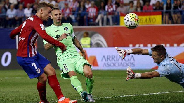 Antonie Griezmann z Atlétika (vlevo) střílí gól brankáři Getafe Vincentovi Guaitaovi.