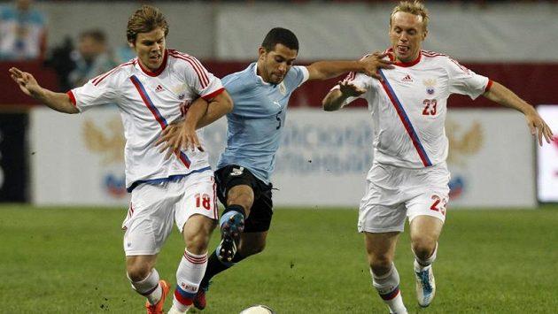 Ruští fotbalisté Alexandr Kokorin (vlevo) a Denis Glušakov v souboji s Garganem z Urugaye