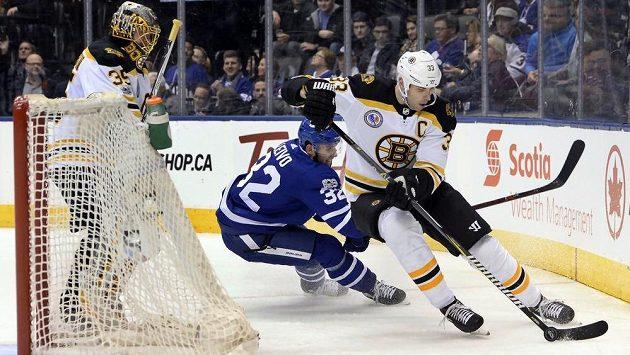 Slovenský kapitán Bostonu Zdeno Chára si kryje puk před dotírajícím Joshem Leivem z Toronta. Přihlíží gólman Bruins Anton Chudobin.