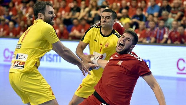 Kiril Lazarov (7) a Nemanja Pribak (21) z Makedonie brání Leoše Petrovského z Česka v úvodním utkání play off kvalifikace mistrovství světa házenkářů.