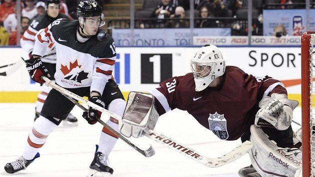 Lotyšský brankář Mareks Mitens zasahuje před Pierrem-Lucem Duboisem z Kanady.