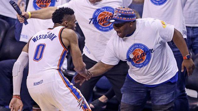 Basketbalista týmu Oklahoma City Thunder Russell Westbrook se raduje s fanouškem během duelu s Golden State Warriors.
