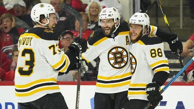 Hokejisté Bostonu Patrice Bergeron (37, David Pastrňák (88) a Charlie McAvoy (73) se radují z gólu proti Carolině ve čtvrtém semifinále play off NHL.