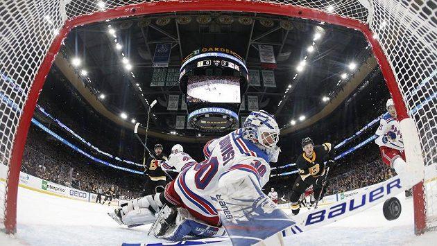 Brankář New York Rangers Henrik Lundqvist se snaží zachytit puk letící do branky v utkání NHL s Bostonem.