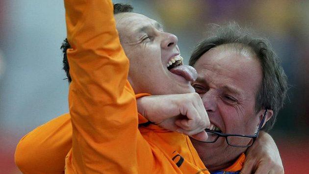 Nizozemský rychlobruslař Stefan Groothuis slaví se svým trenérem olympijský triumf v závodu na 1000 metrů.