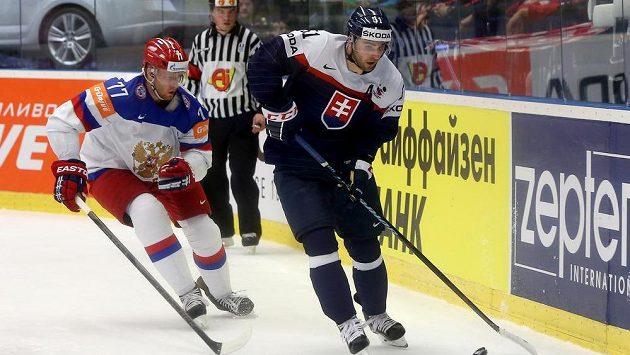 Slovenský obránce Dominik Graňák před Antonem Bělovem z Ruska v utkání na MS v Ostravě.