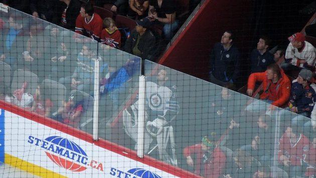 Brankář Winnipegu Ondřej Pavelec (uprostřed) na netradičním místě mezi diváky.